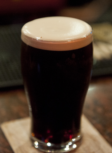 A rich and creamy Guinness with foam still clinging to the rim in a typical Belfast, Northern Ireland