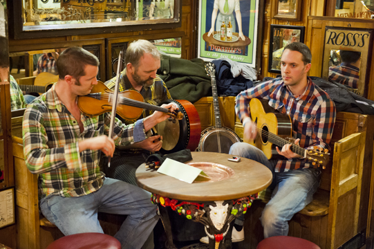 Musicians, a fiddler, guitarist, and drummer on the bodhrán, at the Duke of York, Cathedral Quarter, Belfast, Northern Ireland
