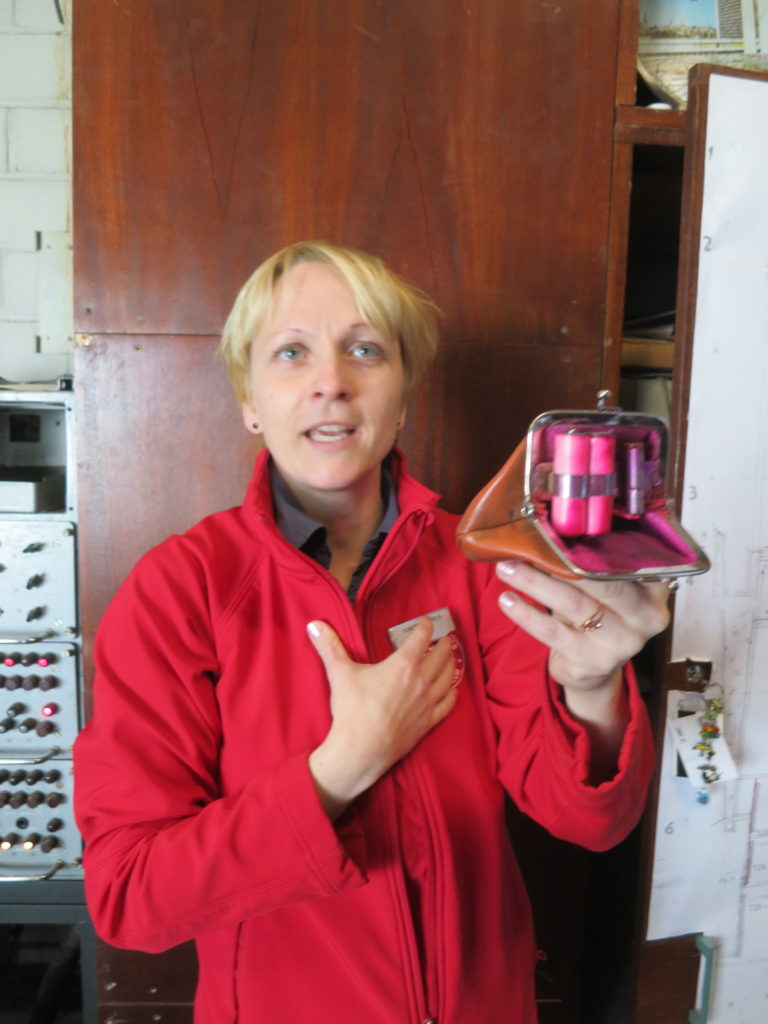 In the radio room, Jana displays a purse rigged with a paint bomb that exploded when the purse was opened. Hotel management used the device to catch employees who might be tempted to find and pocket foreign currency, an offense punishable by imprisonment. Photo by Marc Kristal.