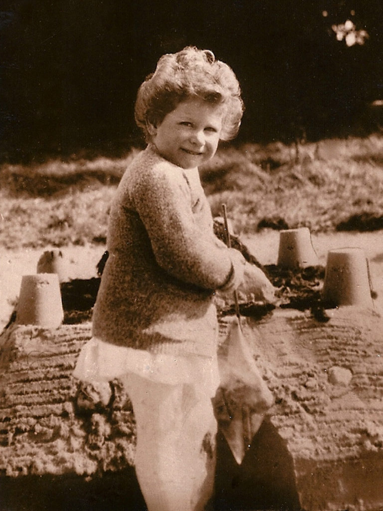 Queen Elizabeth making sandcastle at Craigwell House in Bognor, on view at The Athenaeum Hotel in London this summer.