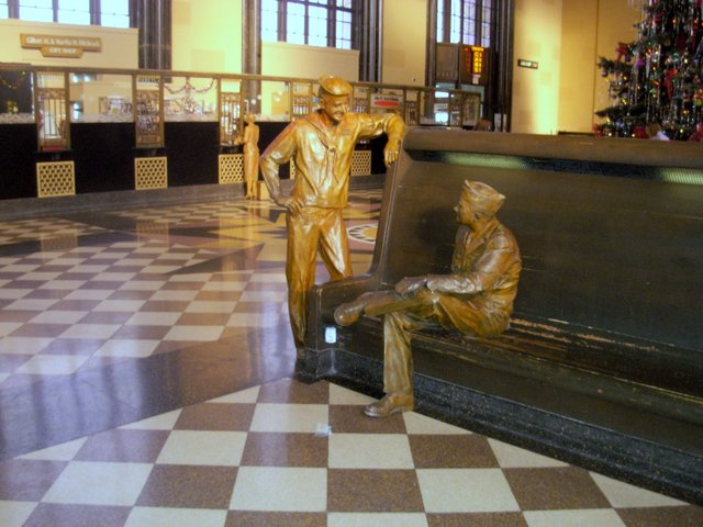 The rows of wooden benches are populated by lifelike bronze statues of World War II servicemen and other travelers who passed through on their way to somewhere else