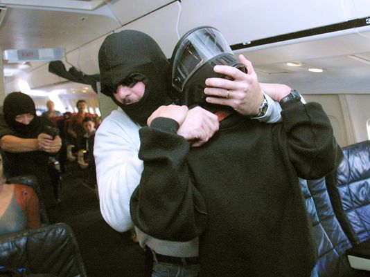 A federal air marshal (far L) fires on a hijacker (C) who is holding a knife to the throat of a flight crew member (R) during a simulation of a hijacking at a tactical training program.(Photo: TOM MIHALEK AFP)