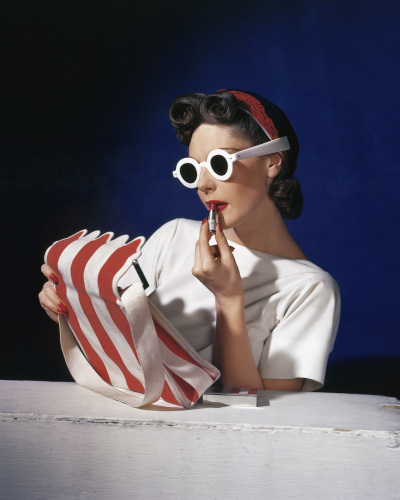 Muriel Maxwell, American Vogue  Artist:   Model Muriel Maxwell in white sunglasses putting on lipstick, wearing red-white-and-blue turban, andv holding a red-and-white striped bag. 1939   Credit line: © Condé Nast / Horst Estate