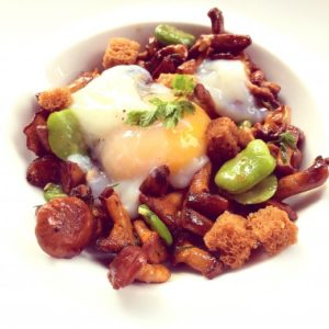 Coddled eggs with girolles and favas.