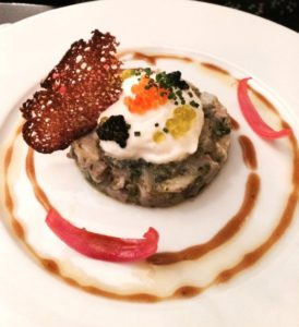 An impeccably fresh sea bass tartare seasoned with seaweed and garnished with several types of fish eggs,