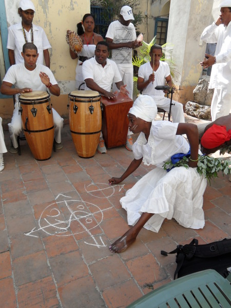 .  Drummers and singers chant while dancer draws symbols to beckon Santeria deities.