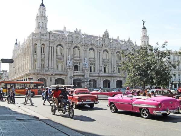An array of Cuba's vintage American cars, newer Russian, Japanese and European models, local buses, and motorized and horse-drawn carriages pass by the spectacular Gran Teatro.