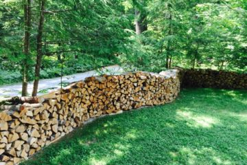 Firewood walls weave around the Migis Lodge property.