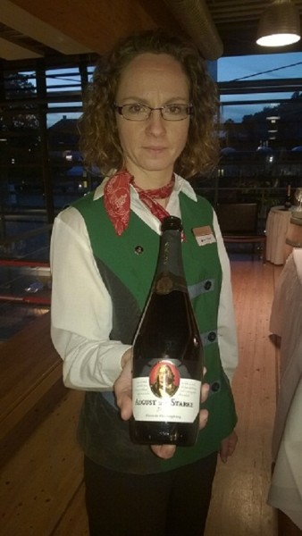 A Schloss Wackerbarth tour guide proudly displays a bottle of August der Starke sparkling wine. PHOTO Monique Burns